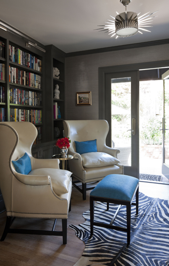 dens/libraries/offices - Benjamin Moore - Rockport Gray - Suzanne Kasler Soleil Flush-Mount Pendant built-ins bookshelves gray walls French doors painted gray ivory leather wingback chairs silver nailhead trim silk teal pillows zebra cowhide rug black ottoman teal blue cushion