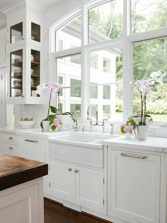 BHG - kitchens - arched window, marble, slab, backsplash, white, wood panel, dishwashers, flanking, farmhouse, sink, Perrin & Rowe, bridge faucet, orchids, white, kitchen island, butcher block, countertops,