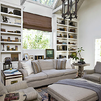 Estee Stanley - media rooms - white, built-ins, bookshelves, open shelving, flanking, window, brown, linen, roman shade, gray, sofa, gray, striped, rolled-arm, chairs. trunk, end table, soft, gray, linen, square, ottoman,
