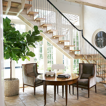 Sunny foyer with white exposed brick walls, fiddle leaf fig plant in woven basket, ...