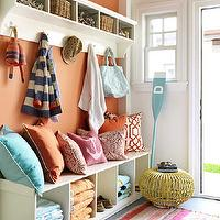 House Beautiful - laundry/mud rooms - pastel, striped, rug, tangerine, walls, white, storage, bench, blue, orange, pink, red trellis, pillows, white, storage, coat rack, mudroom, mudroom design, mudroom cabinets, mudroom storage, mudroom bench, mudroom cubbies, mudroom pin boards, mudroom cork boards, mudroom hooks,