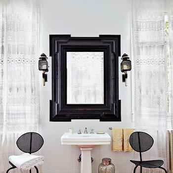 Architectural Digest - bathrooms - glossy, black, fretwork, mirror, glossy, white, pedestal, sink, sconces, yellow, towels, sheer curtains, white sheer curtains, white sheers,