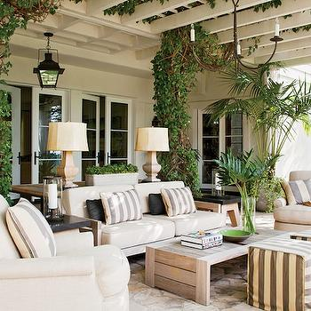 Architectural Digest - decks/patios - French doors, wood, lamps, white, sofa, chairs, white, gray, striped, pillows, white, gray, striped, cube, ottomans, modern, wood, coffee table, iron, lanterns, covered deck, covered patio,