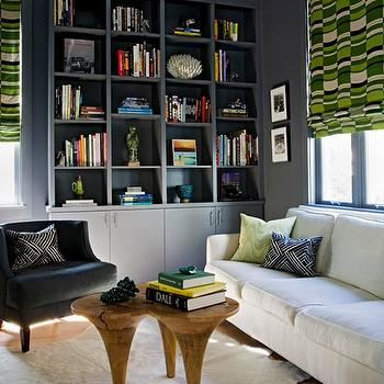 Angie Hranowski - dens/libraries/offices - blue, walls, blue, built-ins, green, roman shades, white, sofa, blue, green, pillows, white, cowhide, rug, blue, velvet, accent chair, blue cabinets, blue built ins, blue built in cabinets,