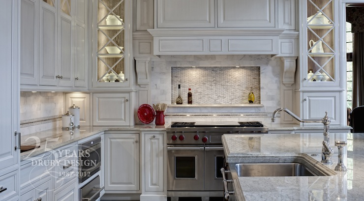 Drury Designs - kitchens - antiqued, white kitchen cabinets, kitchen island, marble, countertops, Wolfe range, stainless steel, warming drawer, marble, subway tiles, backsplash, mosaic, marble, inset, tiles, stainless steel, apron, sink,