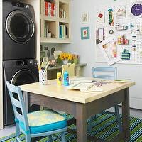 BHG - laundry/mud rooms - baby blue, walls, stacked, gray, front-load, washer, dryer, square, craft. table, teal, blue, chairs, white, peg board,