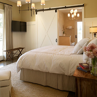 Michael Venera Photography - bedrooms - sliding, barn door, gold, walls, TV, gray, pinch-pleat, drapes, seagrass, rug, white, hotel bedding, gold, stitching, gray, bed skirt, wood, nightstands, barn door, bathroom barn door, interior barn door, Bryant Chandelier, Vendome Chandelier,
