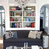 Chic living room with white built-ins, navy blue slipcover sofa, gray flower pillow, ...