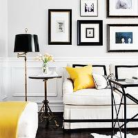 Style at Home - living rooms - chair rail, wainscoting, black, white, cowhide, rug, glass-top, iron, directoire, table, white, rolled-arm sofa, black, ribbon, trim, canary, yellow, pillow, throw, antique brass, pedestal, accent table, antique brass, swing-arm, floor lamp, art gallery,