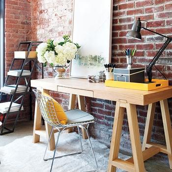 Style at Home - dens/libraries/offices - loft, exposed brick walls, step, bookcase, wood, sawhorse, desk, white, cowhide, rug, yellow, pillow, wood sawhorse desks, sawhorse desks,