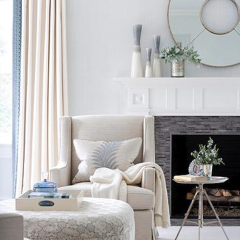 Muse Interiors - living rooms - light, blue, walls, fireplace, black, glass, linear, tiles, white, linen, accent chairs, tripod, table, white, blue, round, ottoman, white, drapes, cream curtains, cream drapes, cream window panels,