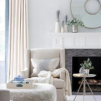 Muse Interiors - living rooms - light, blue, walls, fireplace, black, glass, linear, tiles, white, linen, accent chairs, tripod, table, white, blue, round, ottoman, white, drapes,