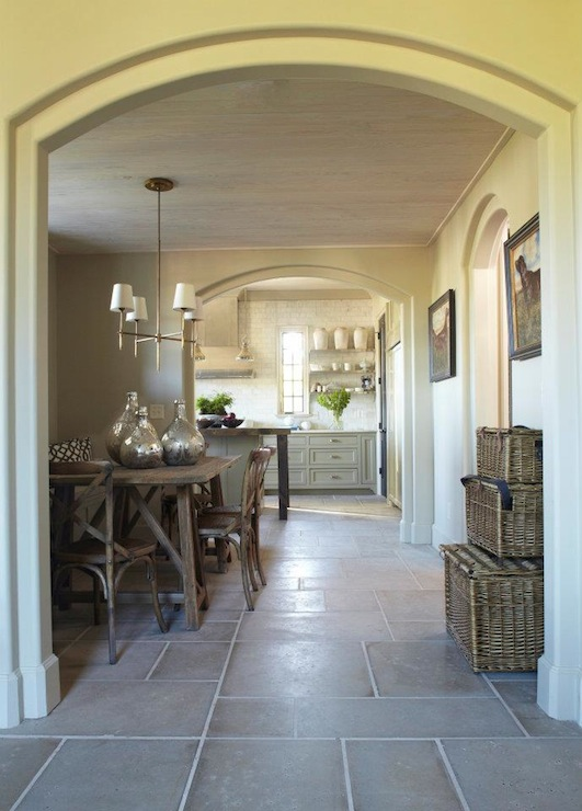 Tracery Interiors - dining rooms - Thomas O'Brien Bryant Chandelier, arched, doorways, built-in, banquette, salvaged wood, dining table, French, cafe, chairs, slate, tiles, floor, stacked, woven, storage, baskets,