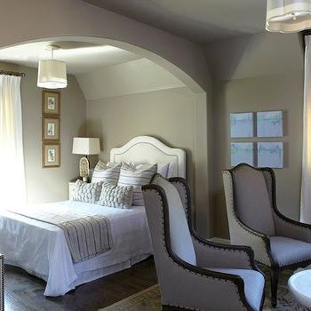Tracery Interiors - bedrooms: warm, gray, walls, white, camelback, headboard, silver, nailhead trim, gray, linen, wingback, chairs, white, drapes, layered, bamboo, roman shades, taupe paint, taupe paint colors, taupe paint color, taupe walls, taupe color paint,