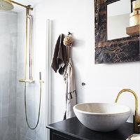 Rustic, vintage bathroom with seamless glass shower, brass rain shower head, ...