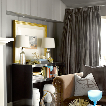 Chic living room with gray paneled walls, silk pinch-pleat gray curtains, glossy ...