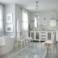 Glamorous master bathroom with gray walls, white mirrored double vanity with white ...