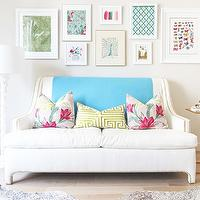 Glam living room with eclectic art gallery, white swoop arm sofa with French brass ...
