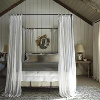 Monochromatic bedroom with white wood paneled walls, gray vaulted ceiling, iron ...