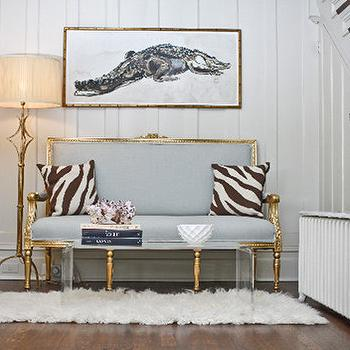 Chic foyer with gray French settee in gold trim, CB2 Peekaboo Clear Coffee Table, ...