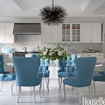 House Beautiful - dining rooms: dining chairs, tufted dining chair, velvet dining chairs, velvet tufted dining chair, blue dining chair, blue tufted dining chair, turquoise dining chairs, turquoise blue dining chairs, oval dining table, lucite dining table, oval lucite dining table, lumiere chandelier, sea urchin chandelier, urchin chandelier, whitewashed floor, whitewashed kitchen floor, whitewashed dining room floor, whitewashed wood floor, open plan kitchen, open floor plan, open floor plan kitchen, white cabinets, white kitchen cabinets, marble countertops, marble subway tile backsplash,
