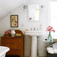 BHG - bathrooms - attic bathroom, cottage bathroom, cottage attic bathroom, sloped ceiling, bathroom sloped ceiling, sloped ceiling bathroom, paneled bathroom, white paneled bathroom, white bathroom paneling, bathroom paneling, white mirror, pedestal sink, bathroom bench, whitewashed bench, vintage cabinet, vintage bathroom cabinet,
