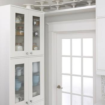Kitchen with white tin ceiling and white glass-front Ikea kitchen cabinets.