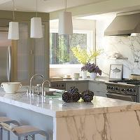 Ken Linsteadt Architects - kitchens - calcutta marble, calcutta marble countertops, calcutta marble backsplash, gray cabinets, gray kitchen cabinets, kitchen with no top cabinets, kitchen with no upper cabinets, stainless steel countertops, waterfall kitchen island, marble kitchen island, waterfall marble kitchen island, frosted glass light pendants, piston stools, modern bar stools, sink in kitchen island, stainless steel appliances, stainless steel shelves, stainless steel kitchen shelves,