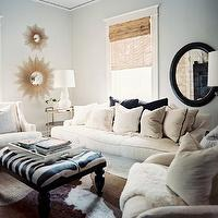 Lonny Magazine - living rooms: blue paint, blue walls, blue paint color, sunburst mirror, stacked sunburst mirrors, gold sunburst mirrors, ivory sofa, ivory chairs, zebra bench, oly studio bench, cowhide rug, tree branch floor lamp, silver tree branch floor lamp, brass end table, tiered end table, oly studio lamp, pipa table lamp,