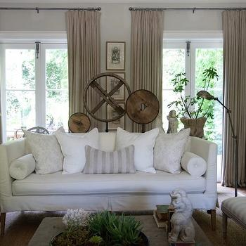 Modern French living room with white slipcovered loveseat, brass pharmacy lamp, ...