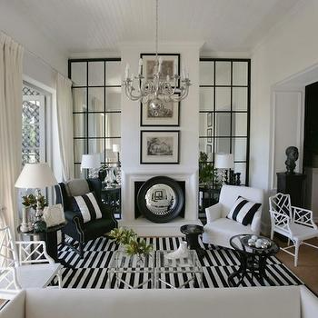 Black and white living room with floor to ceiling paneled mirrors flanking ...