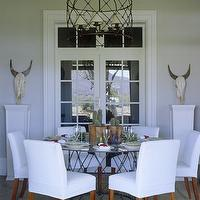 John Jacob Interiors - decks/patios - slipcovered dining chairs, white slipcovered dining chairs, white dining chairs, glass and iron dining table, round dining table, bound sisal rug, iron cage chandelier, cage chandelier,