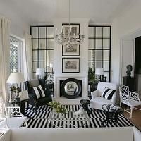 Black and white living room with floor to ceiling paneled mirrors flanking fireplace. ...