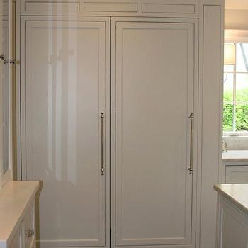 Kitchen with white wood paneled side by side refrigerators.