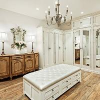 Palm Design Group - closets - walk in closet, closet design, walk in closet design, cool gray walls, gray walls, gray closet walls, white cabinets, wardrobe, white wardrobe, closet wardrobe, white closet wardrobe, mirrored doors, mirrored cabinet doors, mirrored closet cabinet doors, candle chandelier, closet chandelier, walk in closet chandelier, closet ottoman, storage ottoman, white storage ottoman, platinum gray ottoman, gray tufted storage ottoman, gray tufted cushion, gray tufted ottoman cushion, venetian mirror, antique cabinet, buffet lamps, recessed lighting, rustic plank floor,