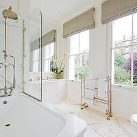 Glamorous master bathroom with glass shower partition over drop-in tub and marble tile ...