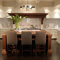 House &amp; Home - kitchens - u-shaped kitchens, two-tone kitchens, chunky wood islands, coffee stained kitchen islands, butcher block tops, square kitchen islands, sink in kitchen island, parsons barstools, brown parsons barstools, brown upholstered barstools, brown barstools, brown counter stools, white kitchen cabinets, white perimeter cabinets, marble perimeter countertops, marble kitchen countertops, marble slab kitchen backsplash, pot fillers, wood kitchen hood, kitchen hood corbels, tv in kitchen, glass cloches, counter-depth refrigerators, dark wood kitchen floors, glass kitchen canisters, bookshelf above fridge, open bookshelf above fridge, open shelving above fridge, wood kitchen beams,