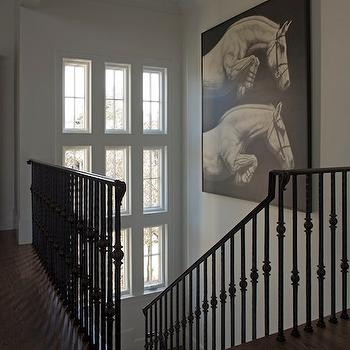 Geoff Chick - entrances/foyers - second floor landings, halls, hallways, iron staircase railings, iron railings, iron spindles, iron staircase spindles, stairwell art, art in stairwells, hallway floors, hallway wood floors, chocolate stained wood floors, horses art, canvas horse art, black stair railing,