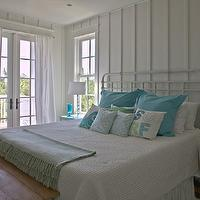 Geoff Chick - bedrooms - white and blue bedrooms, white and blue cottage bedrooms, seaside bedrooms, beach cottage bedrooms, wood panel walls, white wall paneling, french doors, bedroom french doors, cotton drapery, white cotton drapery, cotton window panels, white cotton window panels, white iron beds, queen iron beds, wicker nightstands, turquoise wicker nightstands, stacked glass ball lamps, bedside lamps, glass bedside lamps, turquoise blue pillows, beachy pillows, turquoise accents, turquoise pillows,
