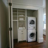 Boor Bridges Architecture - laundry/mud rooms - closet laundry rooms, closet laundry room, hidden laundry room, hidden laundry rooms, stacked washers and dryers, white stacked washers and dryers, white laundry cabinets, marble backsplash, folding doors, closet doors, folding closet doors, laundry room folding doors,
