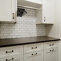 Veranda Interiors - laundry/mud rooms - laundry room cabinets, white laundry room cabinets, shaker cabinets, laundry room shaker cabinets, white shaker laundry room cabinets, honed countertop, black countertop, black honed countertop, honed black countertop, laundry room countertop, black laundry room countertop, honed laundry room countertop, honed black laundry room countertop, black honed laundry room countertop, laundry rod, basket, woven basket, laundry room basket, subway tile iwth dark grout,