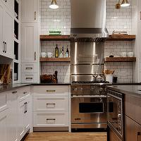 Veranda Interiors - kitchens - microwave nook, kitchen island microwave nook, island microwave nook, library sconces, kitchen library sconces, kitchen hood, floating shelves, brown floating shelves, kitchen floating shelves, brown kitchen floating shelves, floating shelves flanking cooktop, shelves flanking cooktop, white kitchen cabinets, brass kitchen sconces, stainless steel cooktop backsplash, subway tiles, subway tile backsplash, gray grout, gray kitchen grout, kitchen subway tiles, rustic kitchen floor, subway tile with dark grout, subway tile backsplash with dark grout,