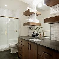 Veranda Interiors - bathrooms - glass shower, brass trim, brass glass shower, black bathroom floor, brushed gold faucet, extra-wide bathroom vanity, extra-wide bathroom cabinet, quartz countertops, black countertops, black quartz countertops, quartz bathroom countertops, black quartz bathroom countertops, floating shelves, floating bathroom shelves, floating shelves flanking bathroom mirror, brown floating shelves, brown bathroom floating shelves, black door, black bathroom door, subway tiles, gray grout subway backsplash, chocolate cabinets, chocolate brown cabinets, chocolate bathroom cabinets, chocolate brown bathroom cabinets, subway tile with dark grout,
