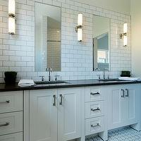 Veranda Interiors - bathrooms - monochromatic bathroom, monochromatic master bathroom white bathroom, white master bathroom, subway tiles, subway tile backsplash, bathroom subway tiles, subway backsplash, gray grout, subway tile grout, gray subway tile grout, modern bathroom sconces, frameless bathrooms, black countertops, black stone countertops, polished stone countertops, polished stone bathroom countertops, black stone bathroom countertops, double sinks, vintage tiles, vintage tiles floor, vintage bathroom floor, white subway tile bathroom,