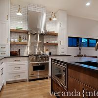 Veranda Interiors - kitchens - two-tone kitchen cabinets, kitchen island sink, microwave nook, island microwave, kitchen island microwave, brown kitchen island, chocolate kitchen island, coffee kitchen island, kitchen library sconces, kitchen floating shelves, brown kitchen floating shelves, floating shelves flanking cooktop, shelves flanking cooktop, white kitchen cabinets, brass kitchen sconces, stainless steel cooktop backsplash, subway tile backsplash, gray grout, gray kitchen grout, kitchen subway tiles, rustic floor, 2 tone kitchen,