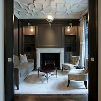Michael Abrams Limited - living rooms - black pocket doors, living room pocket doors, modern pocket doors, taupe wood paneled walls, taupe wood panels, taupe built-ins, taupe fireplace built-ins, fireplace built-ins, taupe bookshelves, taupe shelves, taupe living room shelves, taupe living room bookshelf, taupe built-ins flanking fireplace, ceiling panel, overlay ceiling, geometric ceiling, overlay geometric ceiling, marble fireplace, gray sofa, tufted chairs, gray tufted chairs, oval cocktail table, library sconces, plaster ceiling, geometric ceiling, white geometric ceiling, geometric plaster ceiling,