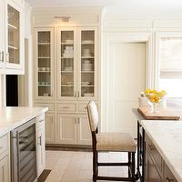 Courtney Hill Interiors - kitchens - floor to ceiling kitchen cabinets, floor to ceiling ivory kitchen cabinets, glass-front china cabinet, gray kitchen island, gray center island, picture lights, kitchen picture lights, wine fridge, wine cooler, sleek kitchen, white kitchen cabinets, shaker kitchen cabinets, white shaker kitchen cabinets, linen shade, kitchen linen shade, roman shade, kitchen roman shade, bridge faucet, kitchen bridge faucet, glass kitchen canisters, marble countertops, glass-front kitchen countertops,