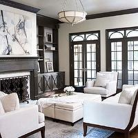 Linda McDougald Design - living rooms: living room ottomans, ottomans, cream ottomans, transom windows, dark gray built-ins, living room built-ins, dark gray built-ins, dark gray living room built-ins, built-ins flanking fireplace, dark gray fireplace, dark gray fireplace mantel, dark gray moldings, crown molding, dark gray crown molding, dark gray living room moldings, dark gray built-in cabinets, dark gray cabinets, dark gray living room cabinets, transitional chairs, transitional sofa, doors, dark gray french doors, gray cabinets, gray built ins, gray built in cabinets, gray living room cabinets, gray living room built ins,
