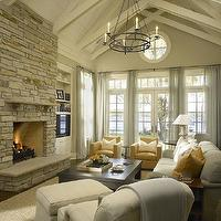 Hickman Design Associates - living rooms - transitional living room, vaulted ceiling, cathedra ceiling, brick fireplace, hearth, brick hearth, built-ins, living room built-ins, built-ins flanking fireplace, TV, TV nook, built-in TV nook, french doors, transom windows, sheers, window sheers, blue sheers, blue window sheers, ivory built-ins, ivory built-in cabinets, candelabra, living room lighting, light gray sofa, light gray chair, yellow pillows, mustard yellow, mustard yellow chairs, jute rug, wood beams, living room wood beams, brick fireplace, floor to ceiling fireplace, floor to ceiling brick fireplace,