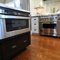 Kitchen Studio of Glen Ellyn - kitchens - microwave nook, kitchen island microwave nook, kitchen island microwave, island microwave nook, island microwave, kitchen oak wood floor, two-tone kitchen, two-tone cabinets, two-tone kitchen cabinets, perimeter cabinets, white perimeter cabinets, kitchen island, black kitchen island, calcutta marble countertops, chevron tiles, chevron tile backsplash, chevron kitchen tiles, chevron kitchen backsplash, chevron backsplash tiles, chevron cooktop tiles, chevron cooktop backsplash, buil tin microwave nook,